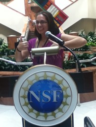 Emily, giving thumbs-up, at podium with NSF logo.