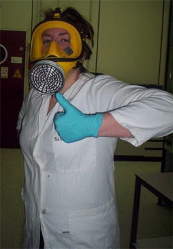 Emily wearing full-face respirator, white lab coat and cyan latex glove, giving thumbs-up.