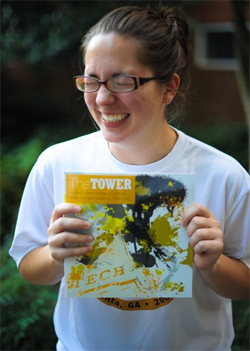 Emily with big smile and eyes closed, holding up a copy of The Tower.